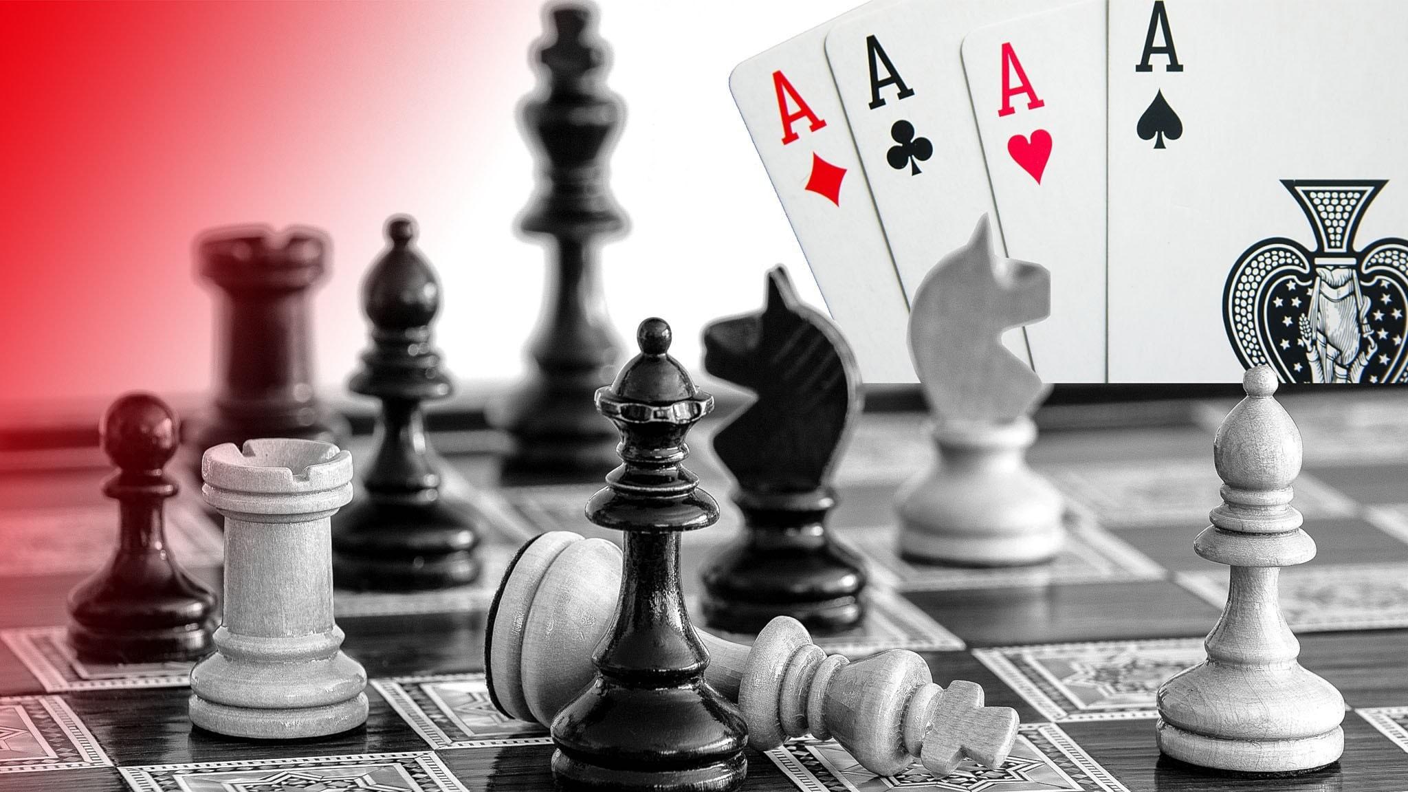 Schackbräde med schackpjäser och fyra ess från en kortlek i bakgrunden.