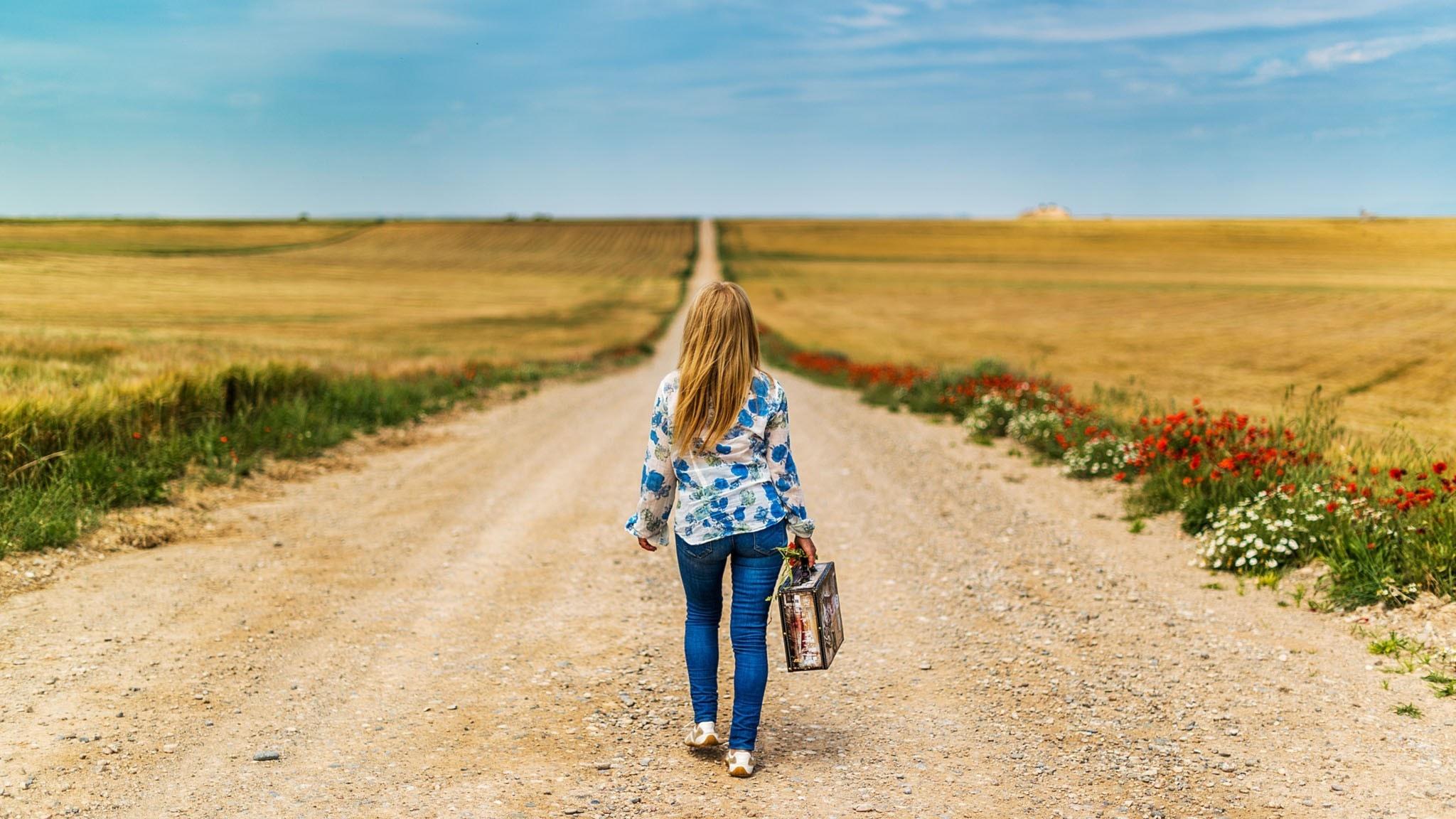 Flicka med resväska som går på en väg mot horisonten.