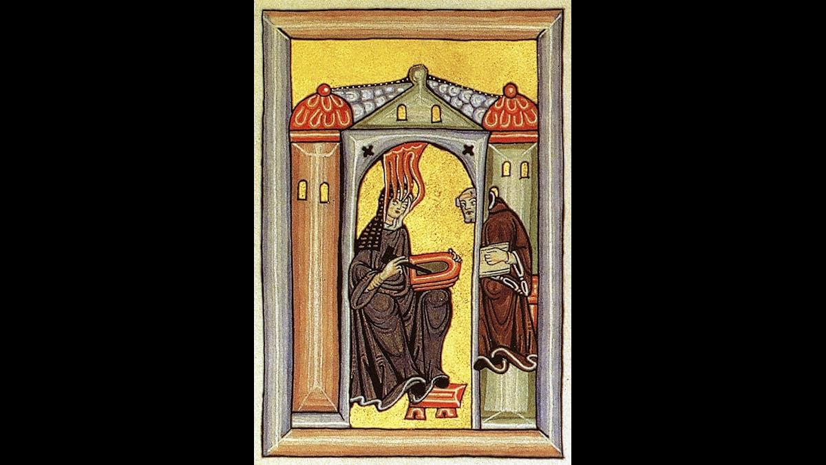 Hildegard får sina uppenbarelser - och melodier - från Gud. Hon dikterar dem för den lärde munken Volmar som nedtecknar dem.