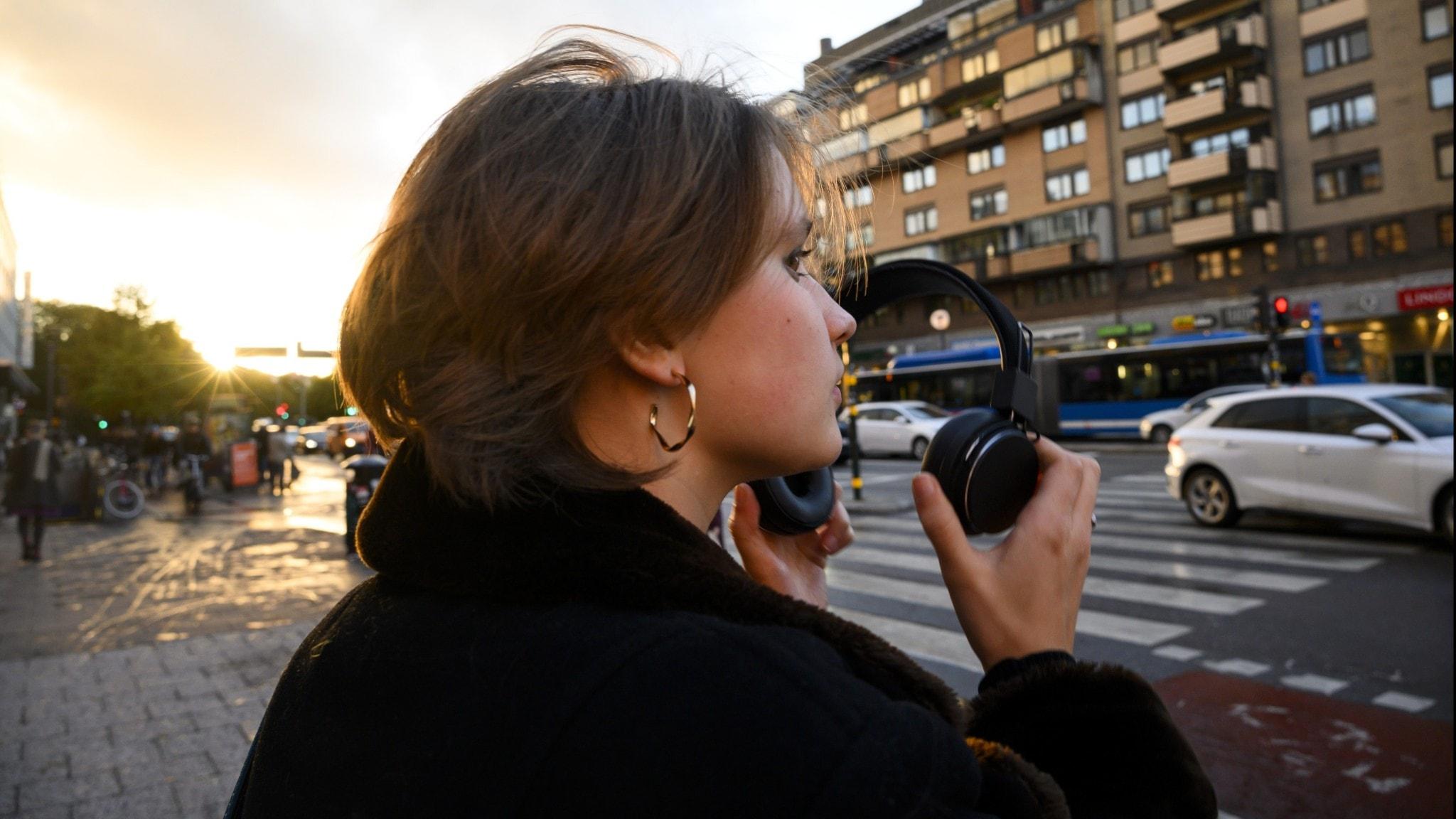 Bild: Person som håller i hörlurar i offentlig miljö.