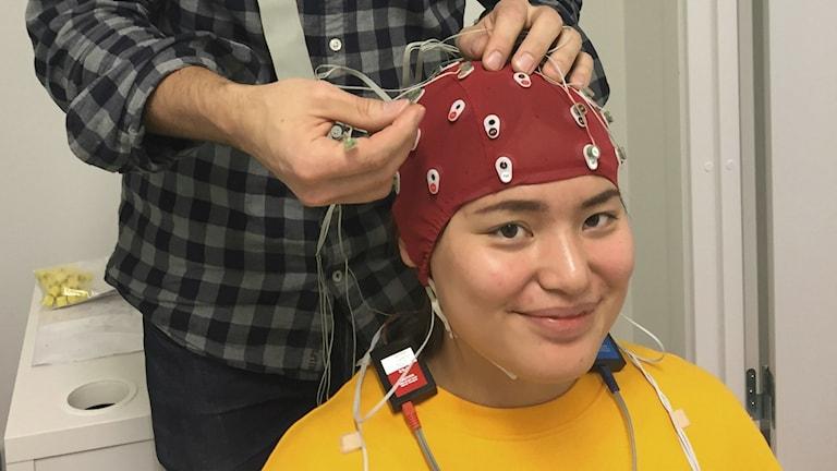 Sonja Levin sitter på en stol. På hennes huvud har hon en röd hätta, i vilken elektroder är fästade.