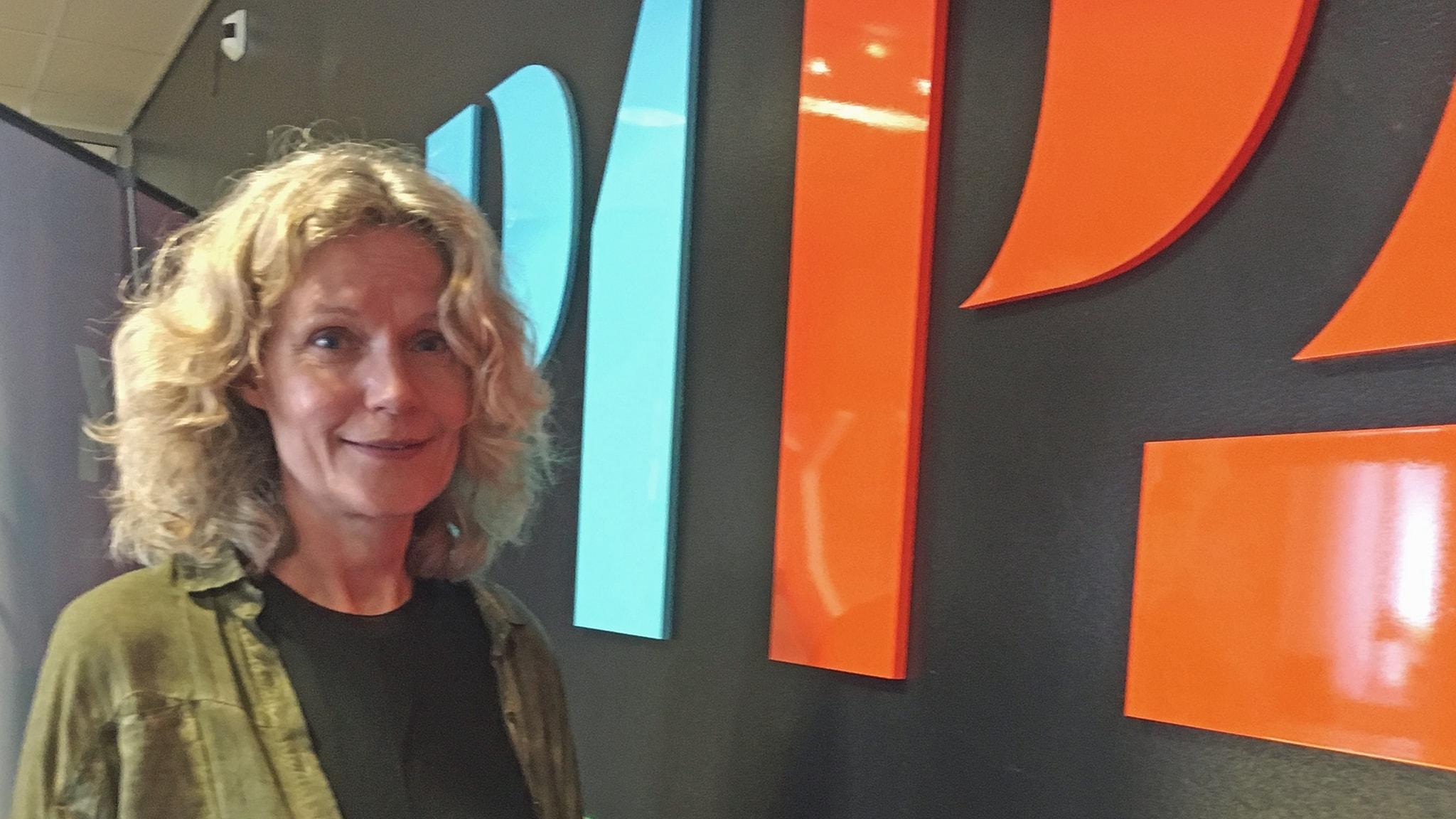 Åsa Wikforss framför P1 pch P2-loggorna i Upplands radiohus