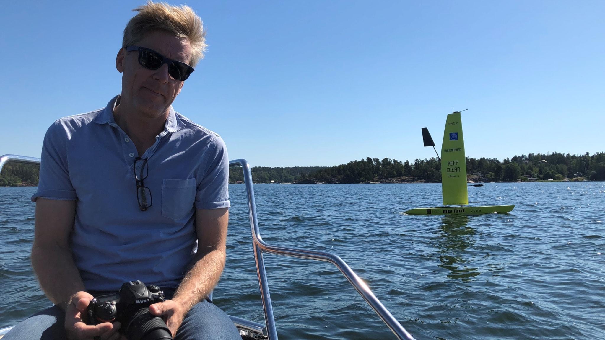 Jakob Kuttenkeuler sitter på ett båtdäck med en kamera i handen. I bakgrunden syns den gula självseglande båten.
