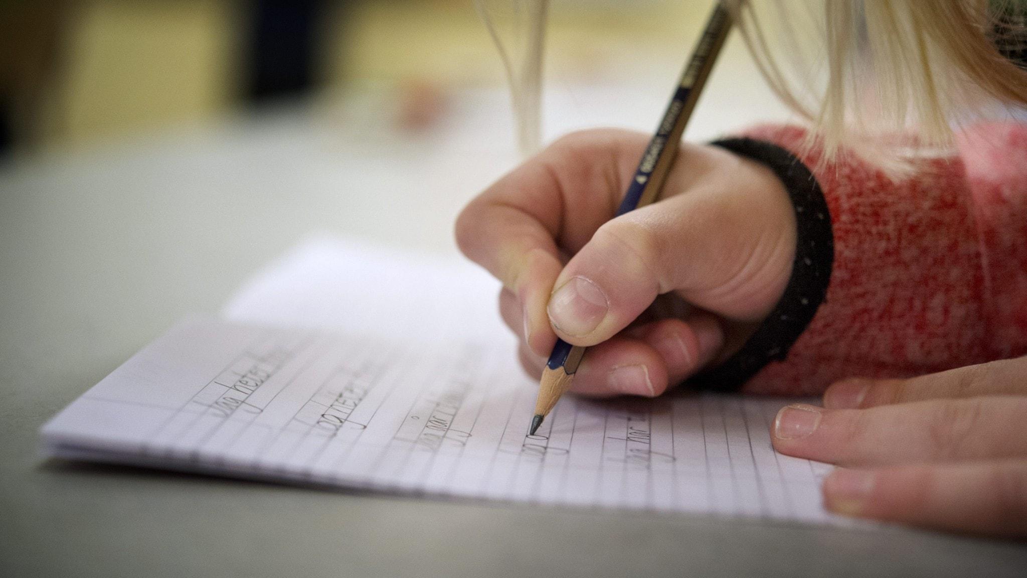 En lågstadieelev skriver på ett papper med en penna.