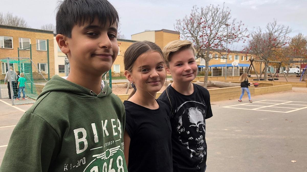 Femteklassarna Ibrahim Monati, Engla Khalaf och Hampus Lönn på Käpplundaskolans skolgård.