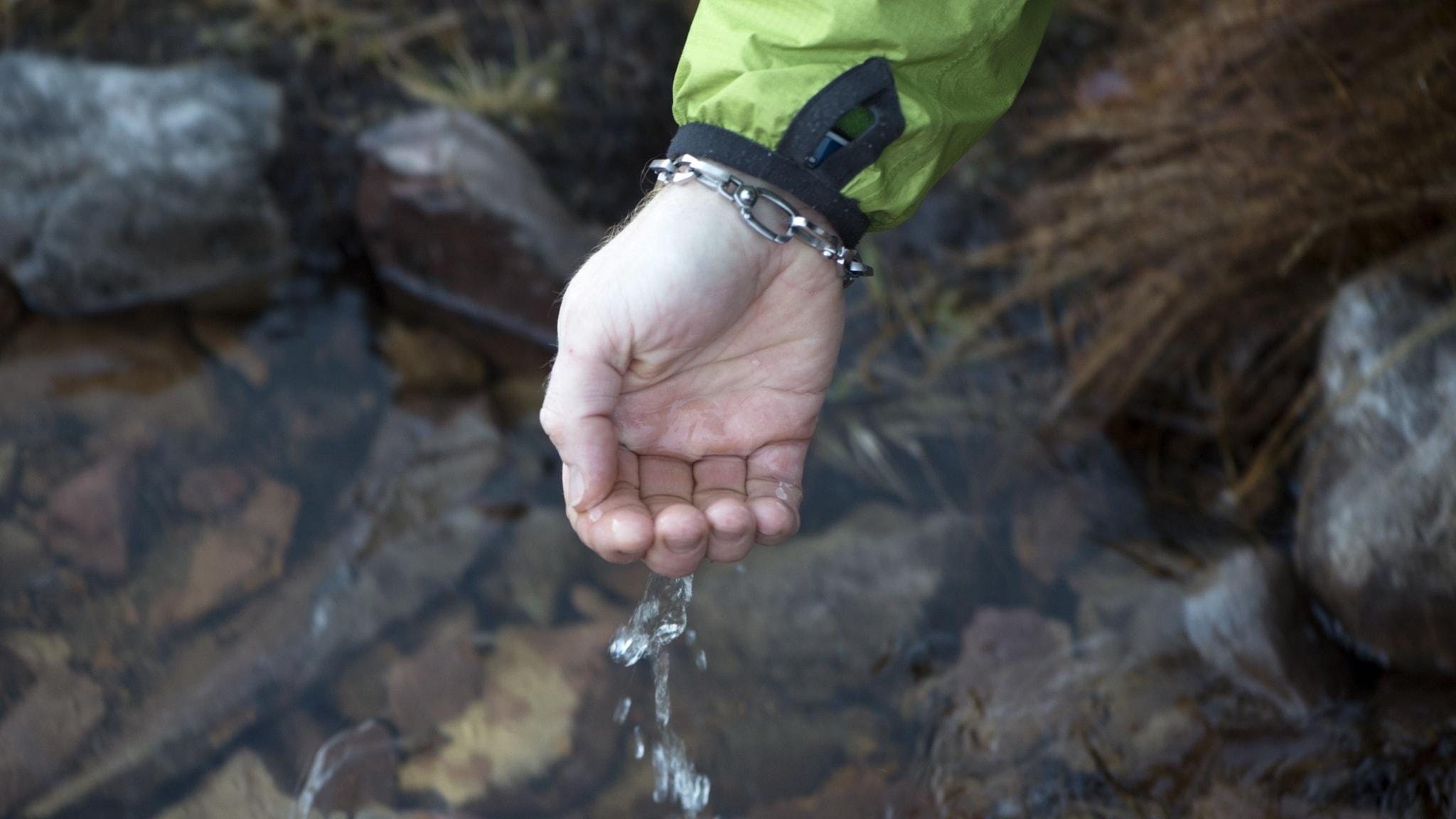 en skopad manshand hivar upp vatten ur en fjällbäck