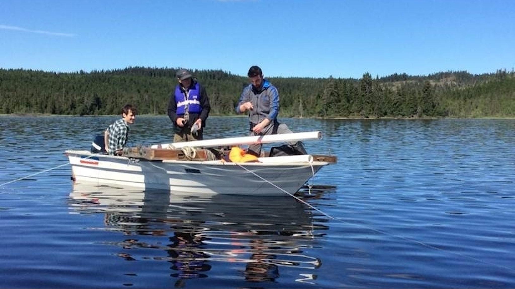 Tre personer i en roddbåt på en sjö håller i ett stuprör