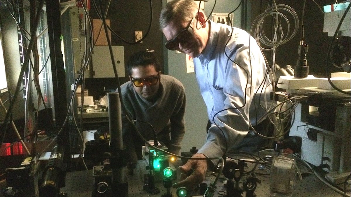 W.E. Moerner och forskarmedarbetaren Saumya Saurabh justerar en experimentuppställning.