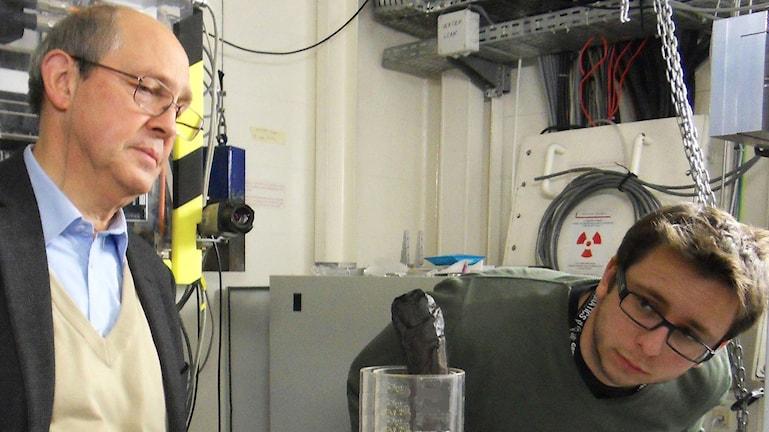 Två forskare ser på en förkolnad skriftrulle som står i en genomskinlig cylinder.