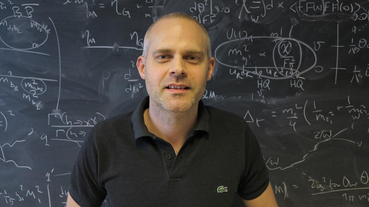 Christoffer Petersson framför tavla med matematiska formler. Foto: Johannes Björnerås/Sveriges Radio