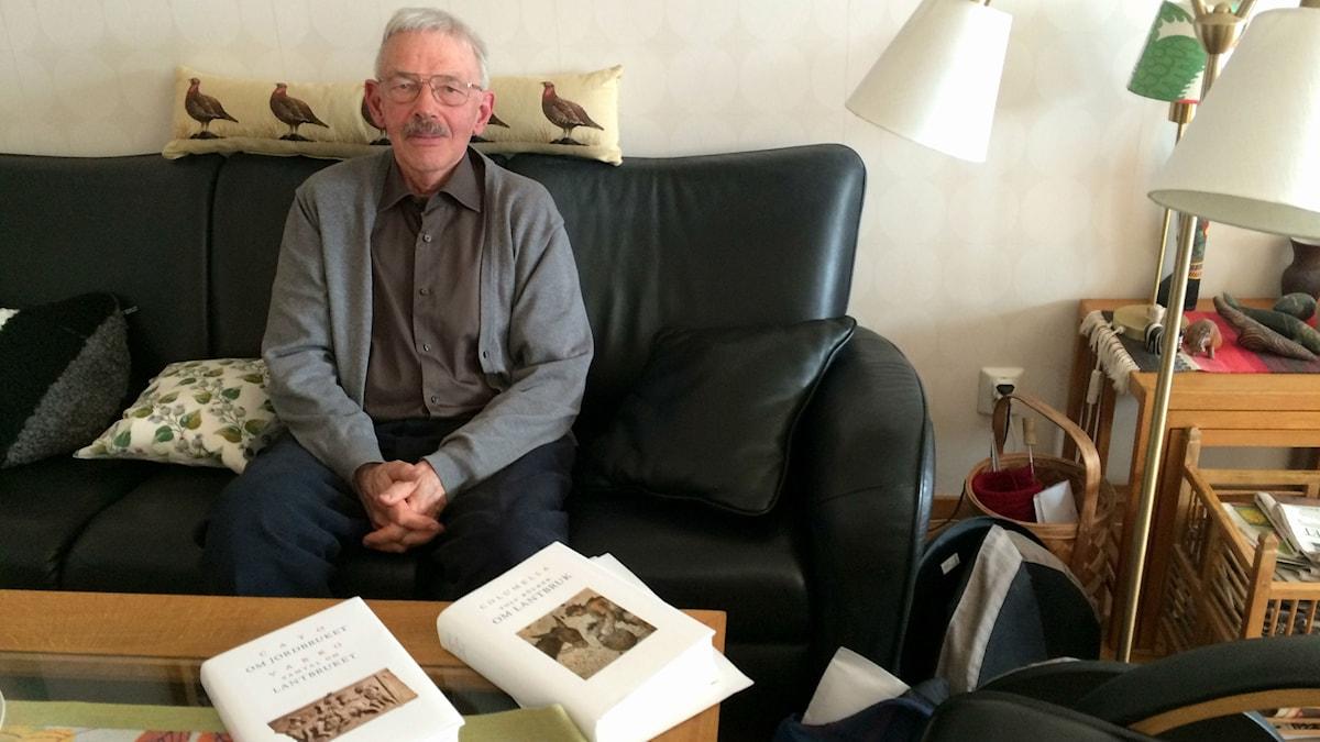 Sten Hedberg i soffa framför bord med böcker