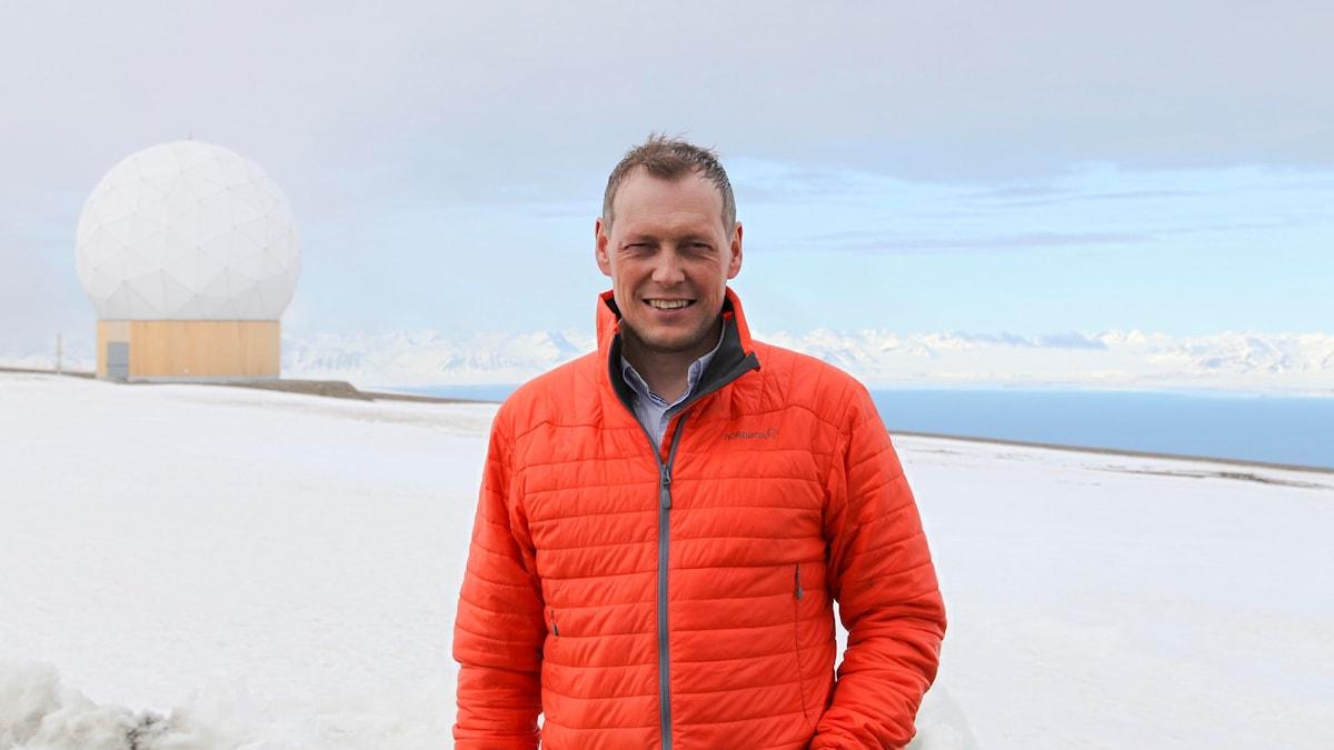 Stationschefen Ole Petter Storstad framför en av tiotalet stora antennradomer på satellitstationen på Svalbard