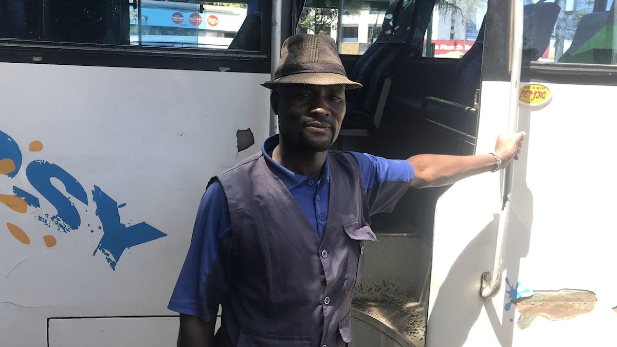 En man i solhatt lutar sig mot sin minibuss
