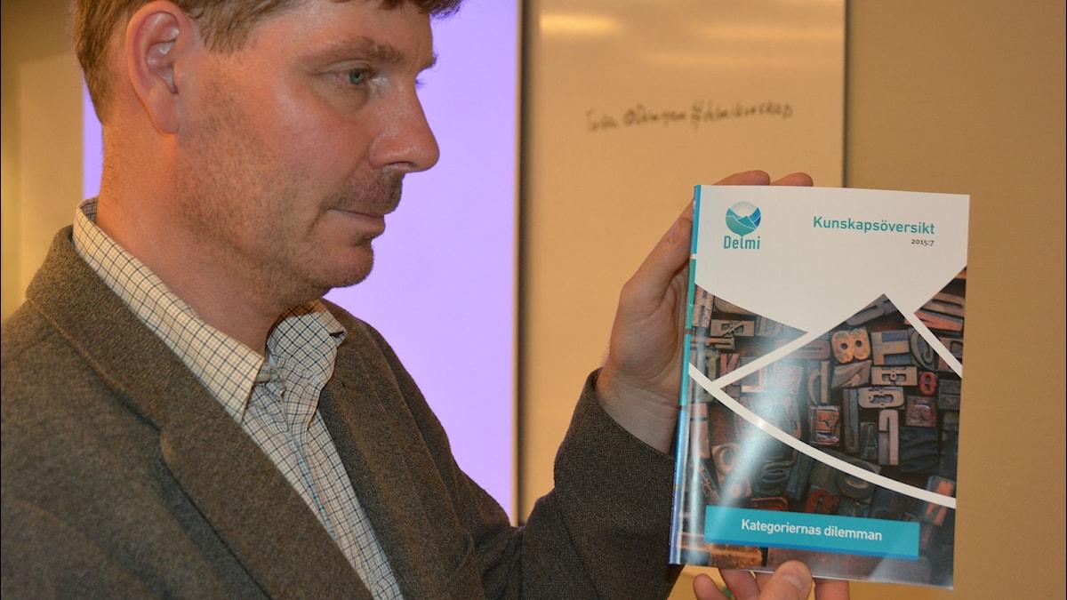Per Strömblad  håller upp boken Kategoriernas dilemma. Foto: Niklas Zachrisson/Sveriges Radio