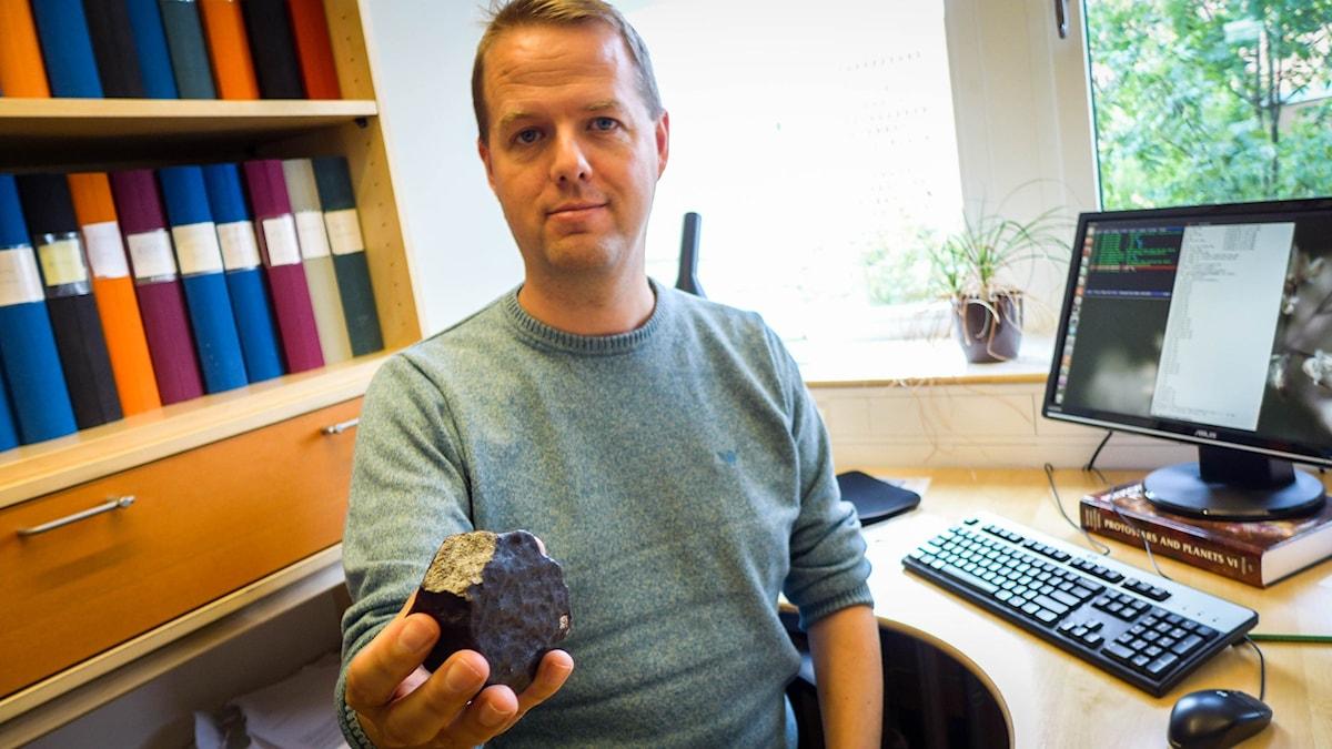 Anders Johansson håller upp små meteoritbitar