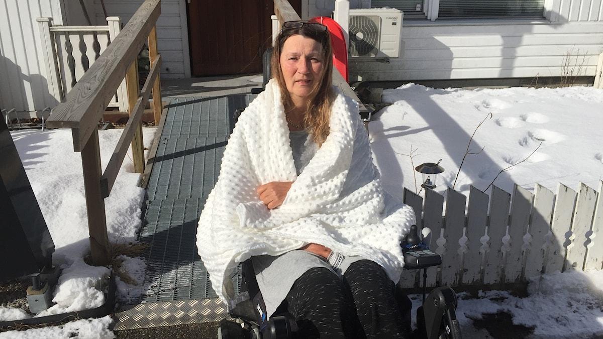 En kvinna sitter i solskenet utanför sitt hus med en filt om axlarna
