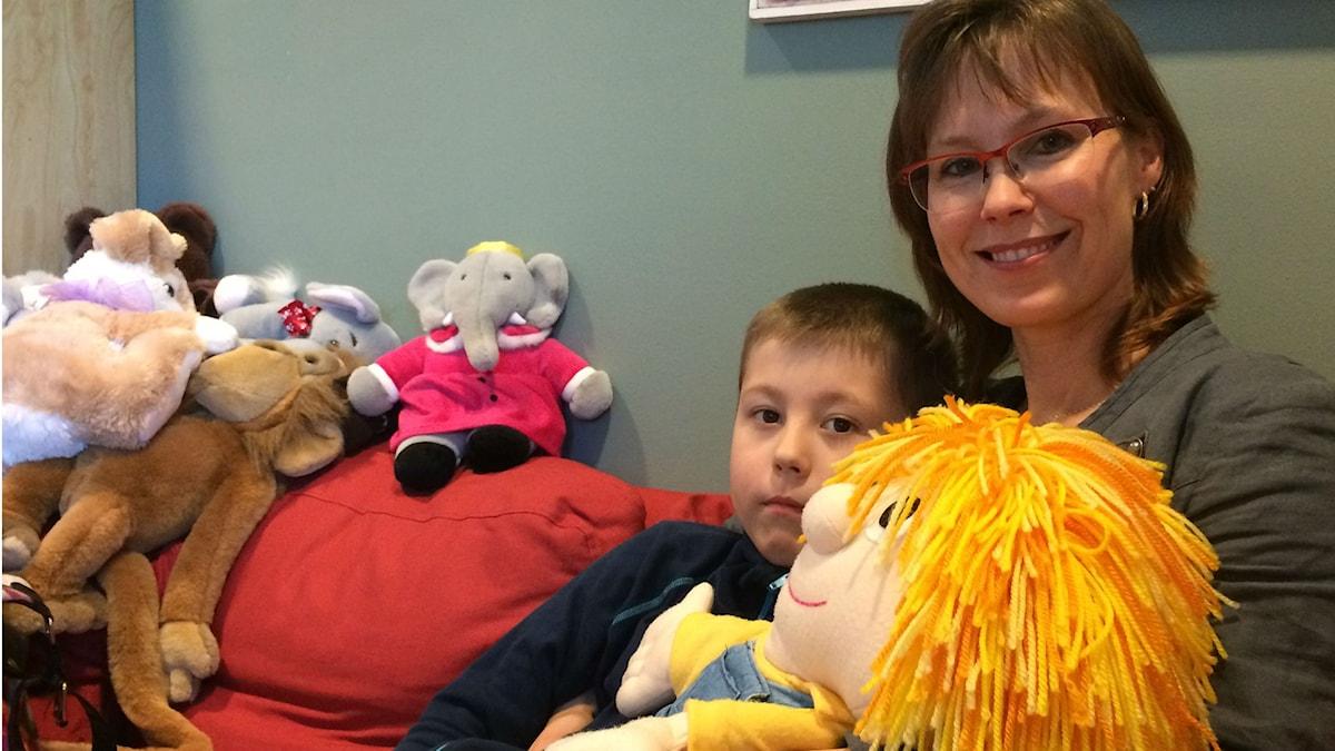 Felix Lundblad med mamma i soffa med nallar