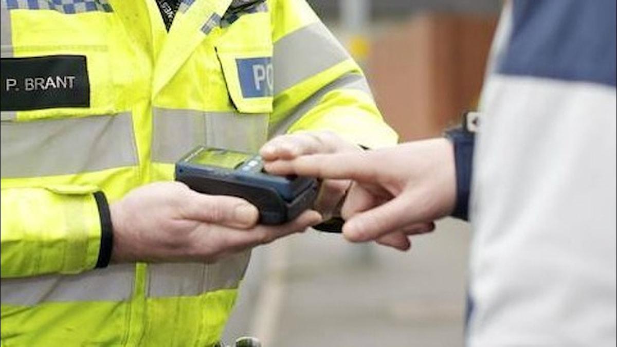 Brittisk polis tar fingeravtryck för identifiering.