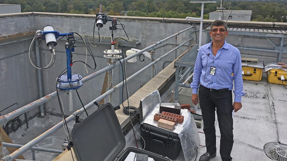 Forskaren ler bredvid utrustning