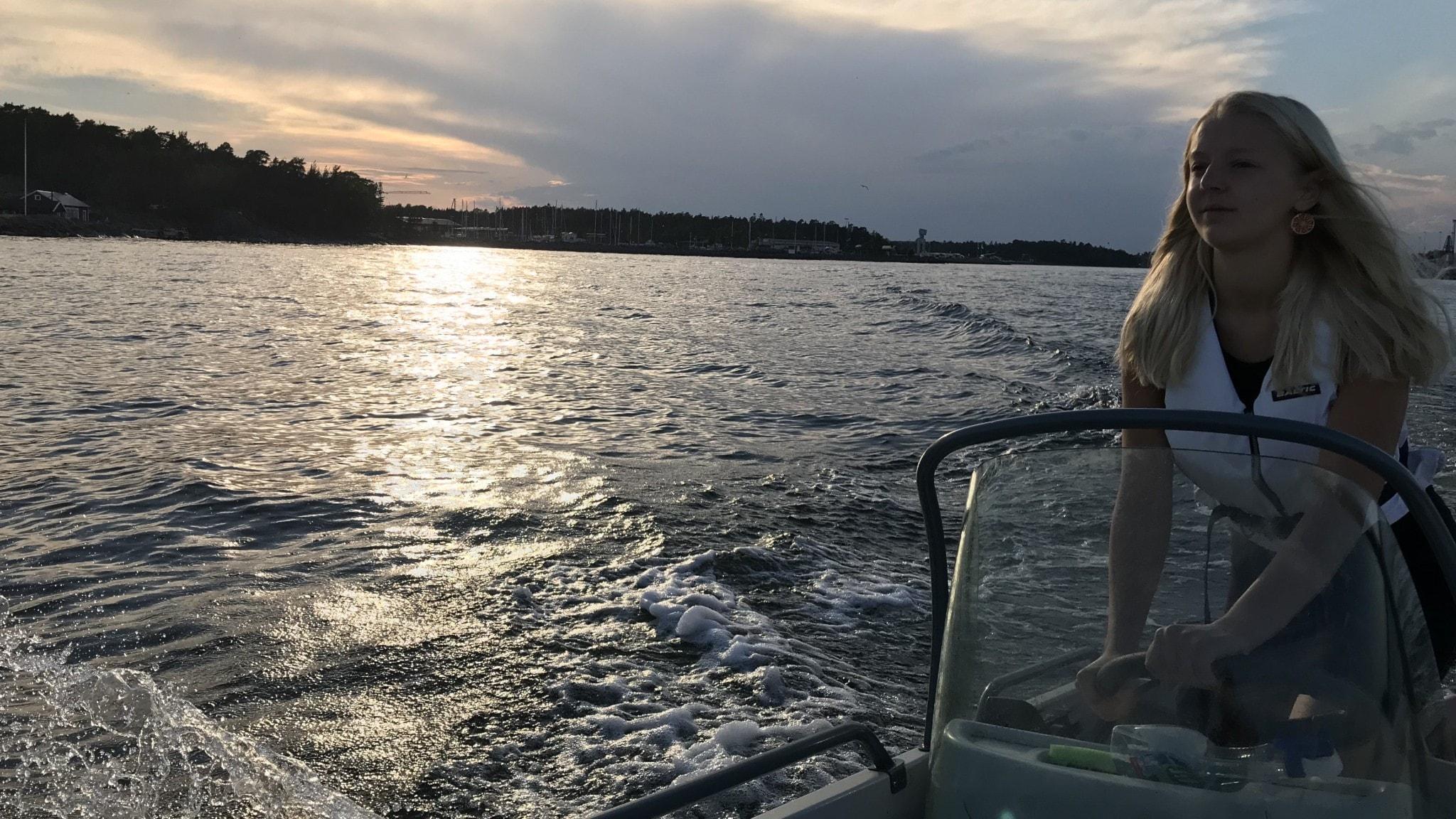 Kvinna kör motorbåt på havet