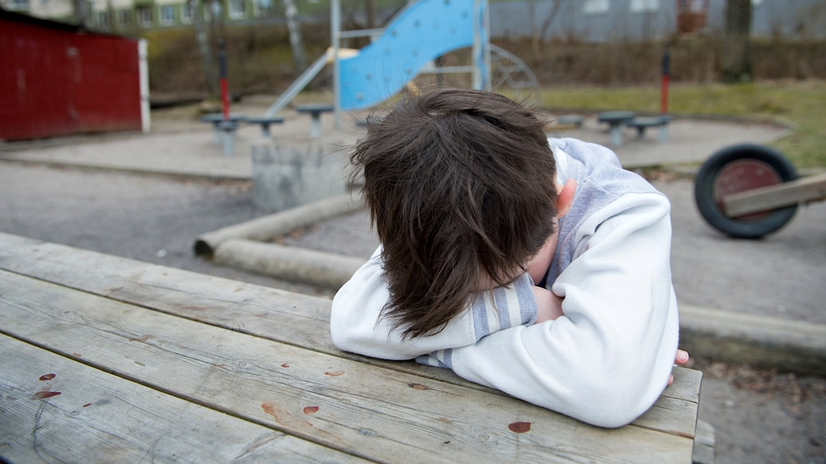 En pojke sitter med huvudet i sina armar och är ledsen.