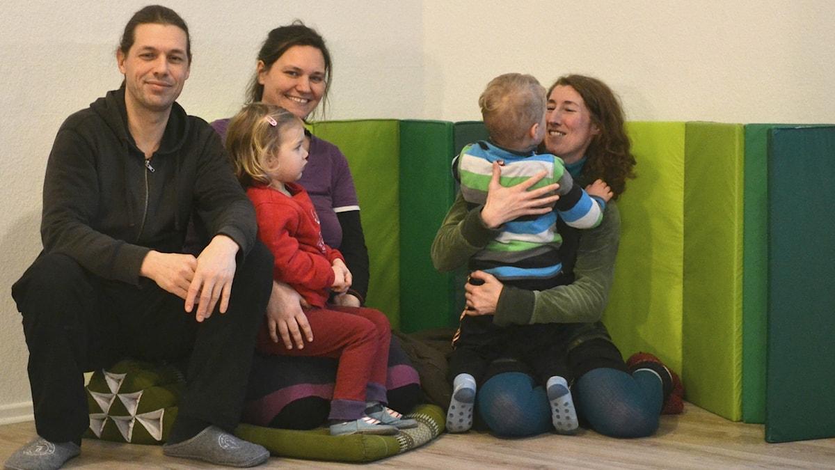 Tre föräldrar sitter på golvet omgivna av gröna, tygklädda kuddar. Två barn sitter i deras knä.
