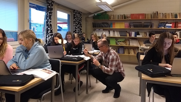 En lärare sitter på huk i klassrummet vid en elevbänk och hjälper till i skolarbetet.