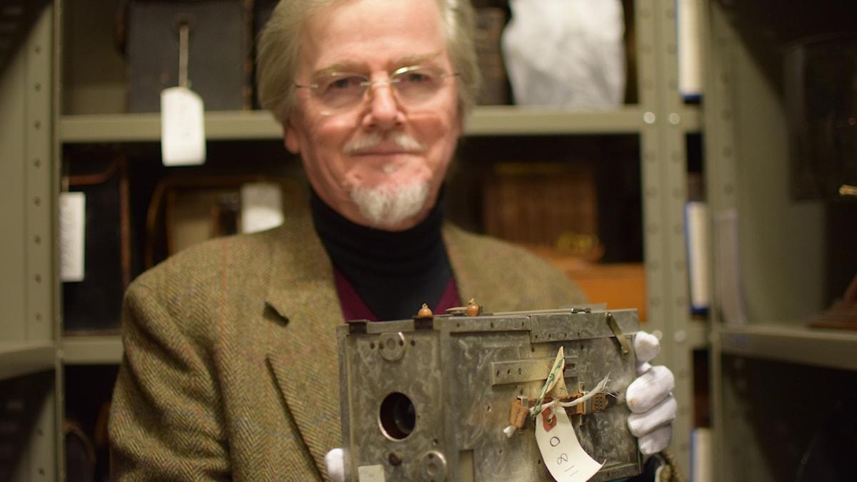 Björn Axel Johansson håller fram en plåtkamera från 1800-talet.