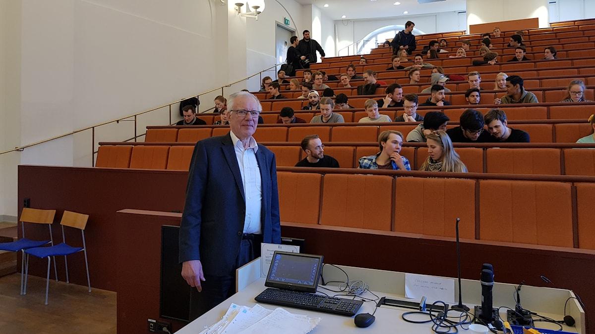 En äldre man framför en sal med studenter