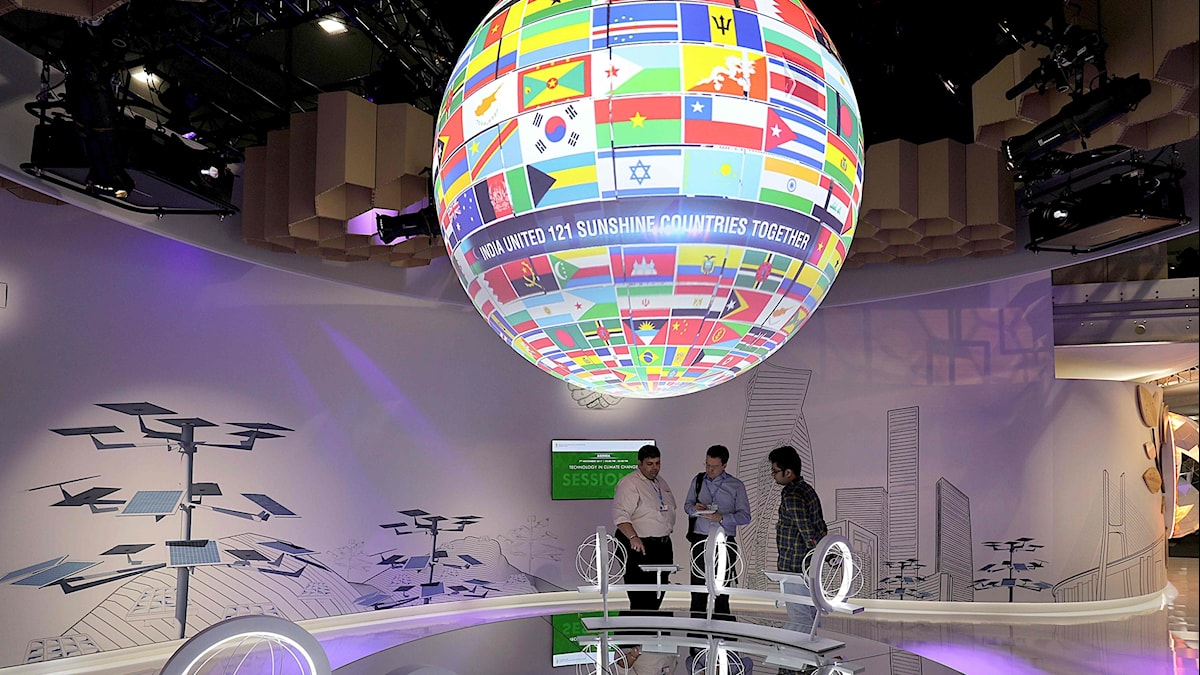 besökare vid en glob bestående av deltagarnas flaggor.
