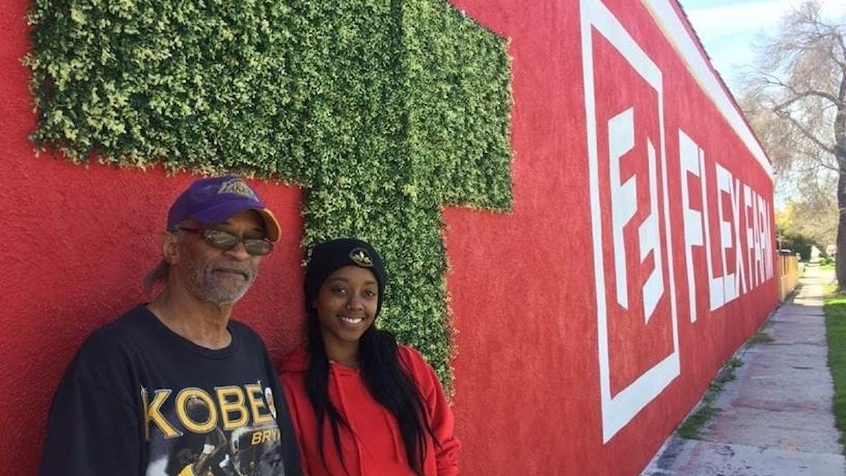 En man och en kvinna framför en röd mur med grön klängväxt.