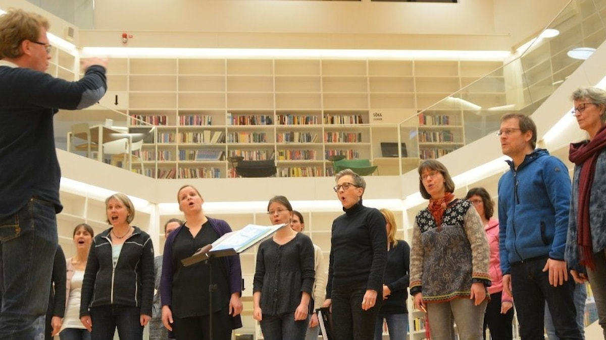 David Lundblad dirigerar sin kör i ett bibliotek.