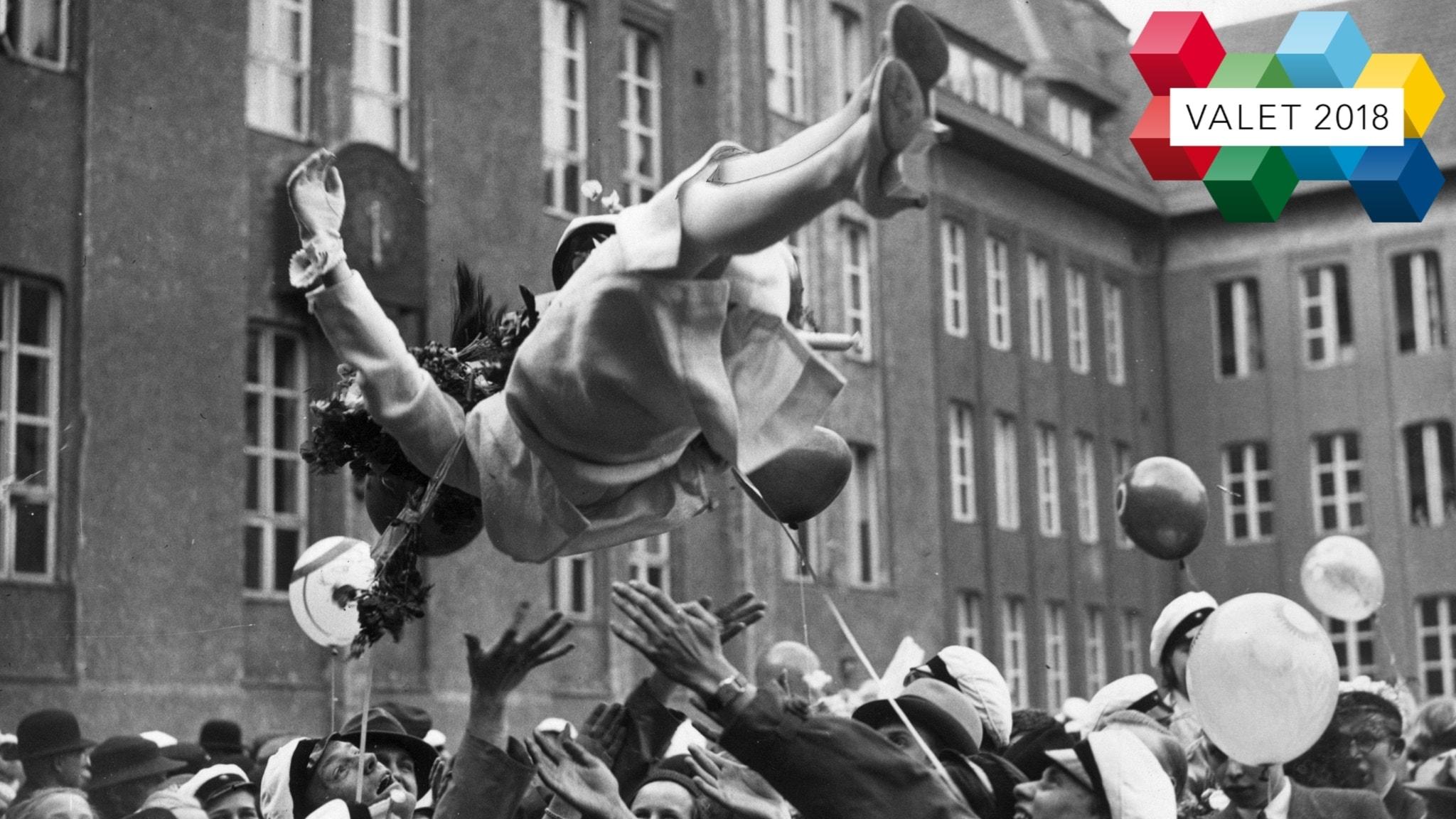 En student hissas i luften av sina klasskamrater.