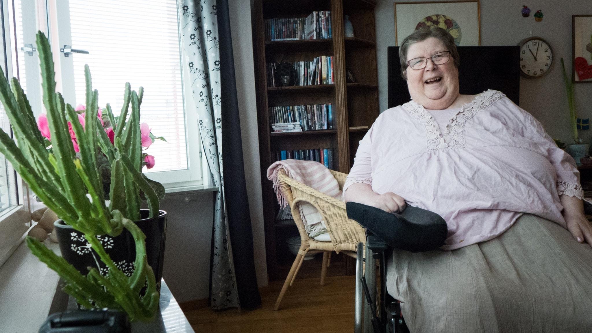 En glad äldre kvinna vid sitt fönster