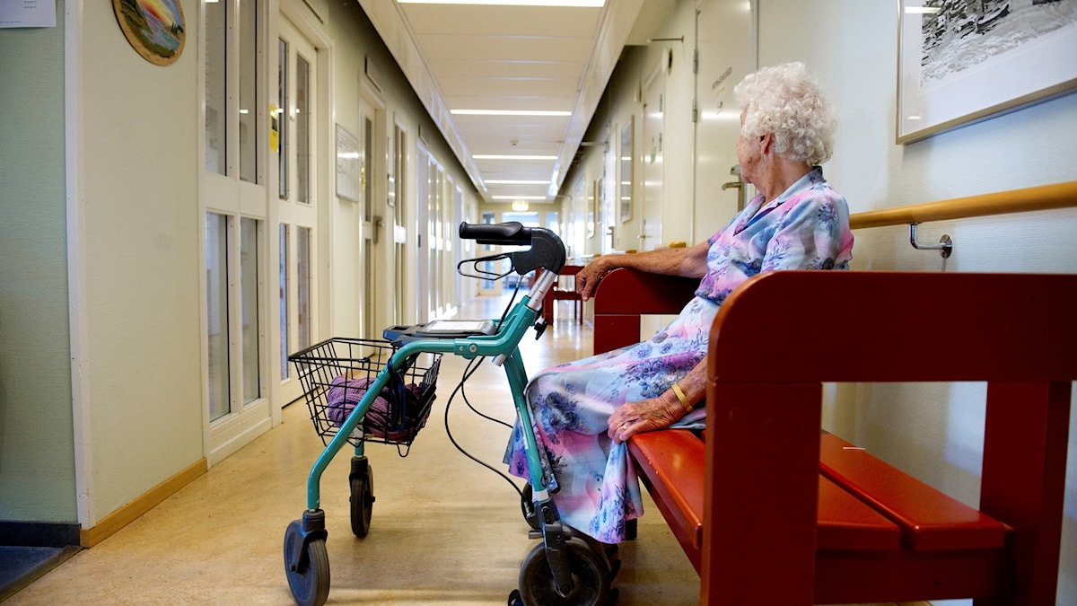 äldre kvinna sitter på en bänk