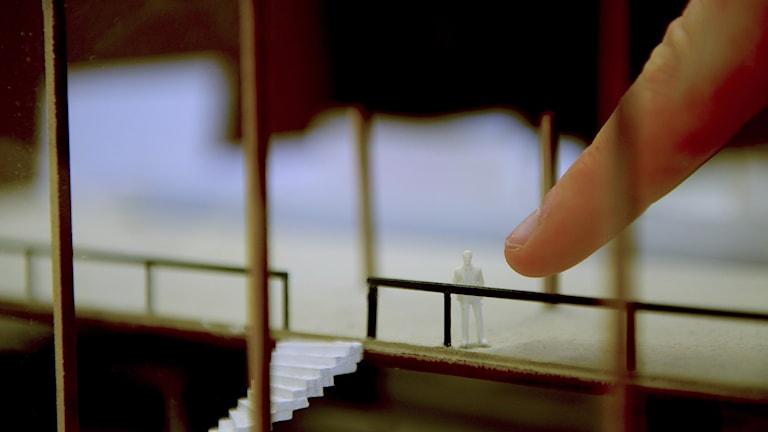 Finger som pekar mot liten människa