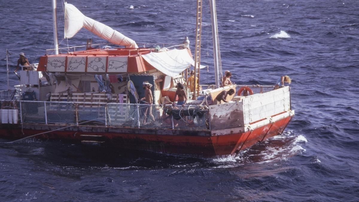 En flotte på ett hav. Flera personer rör sig på flotten.