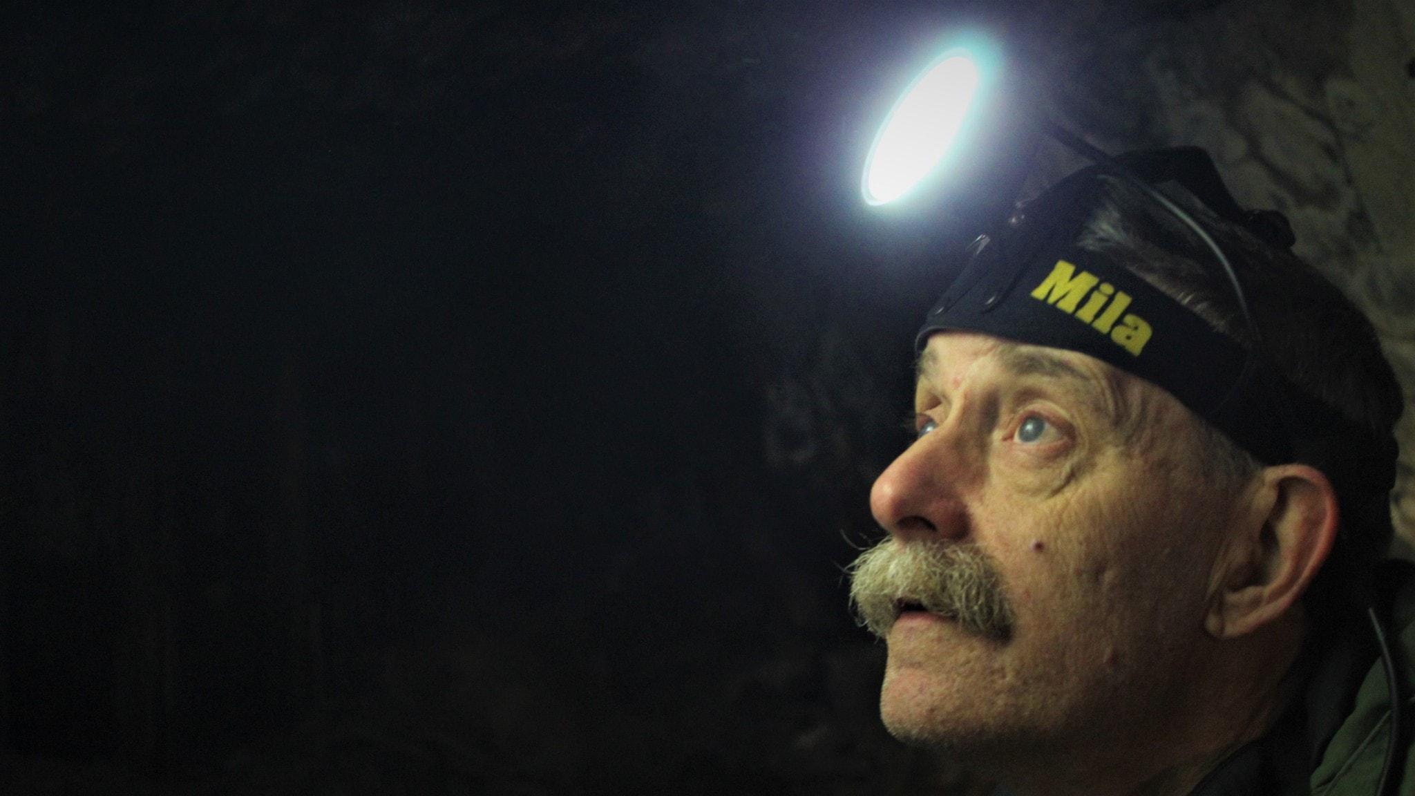 Johnny de Jong, fladdermusforskare, i grotta med pannlampa.