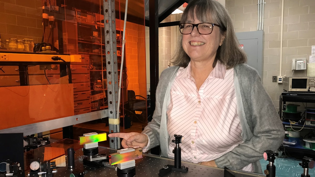 Donna Strickland pekar på ett regnbågsfärgat litet block i sitt laserlaboratorium