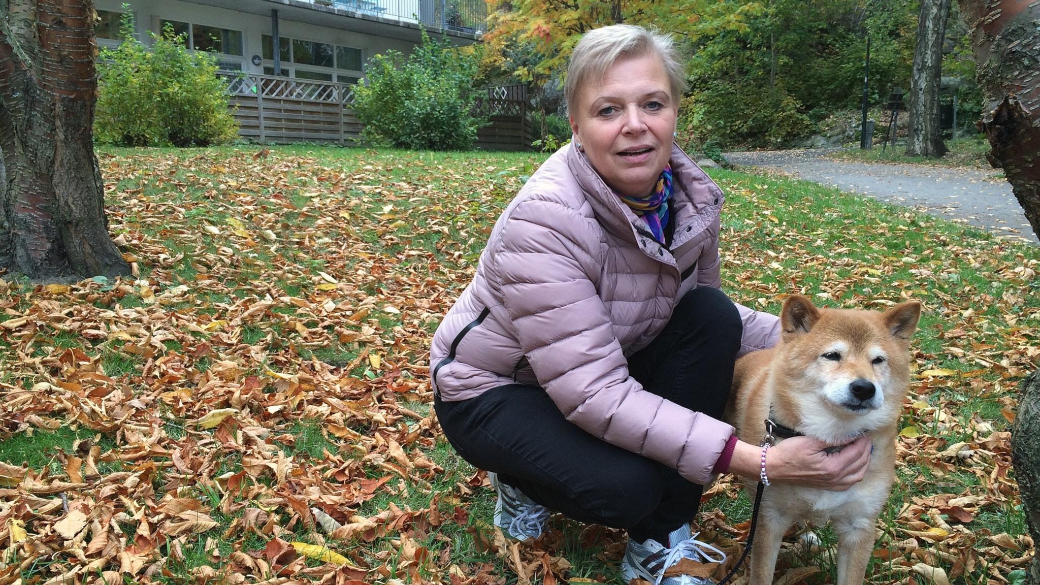 Annelie Grip sitter på huk i hästlöv med sin hund