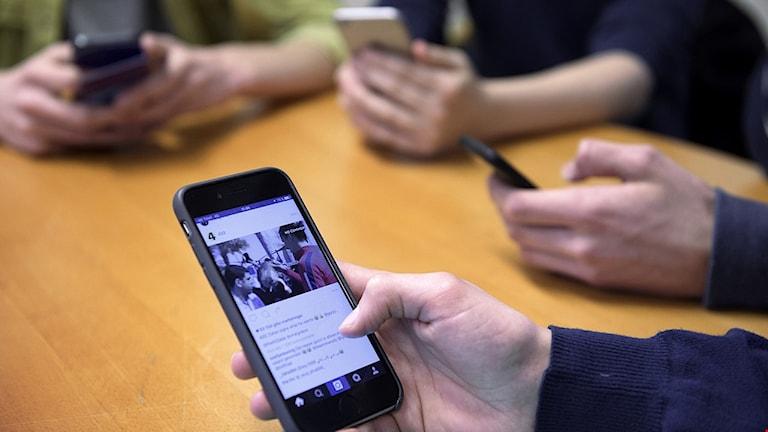 Personer med mobiltelefoner runt ett bord