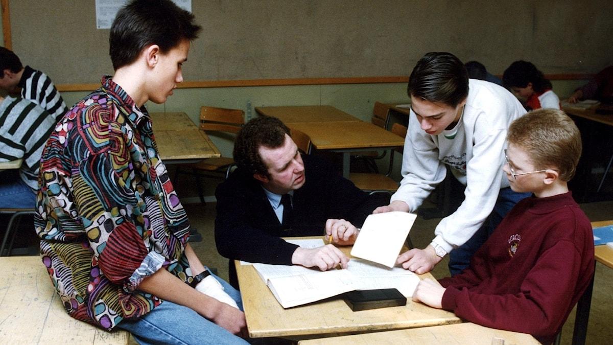 En lärare står på huk och förklarar för några pojkar som står/sitter runt om.