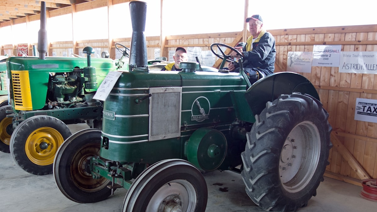 Man sitter på gammal traktor av märket field marshall på Vikstas traktormuseum.