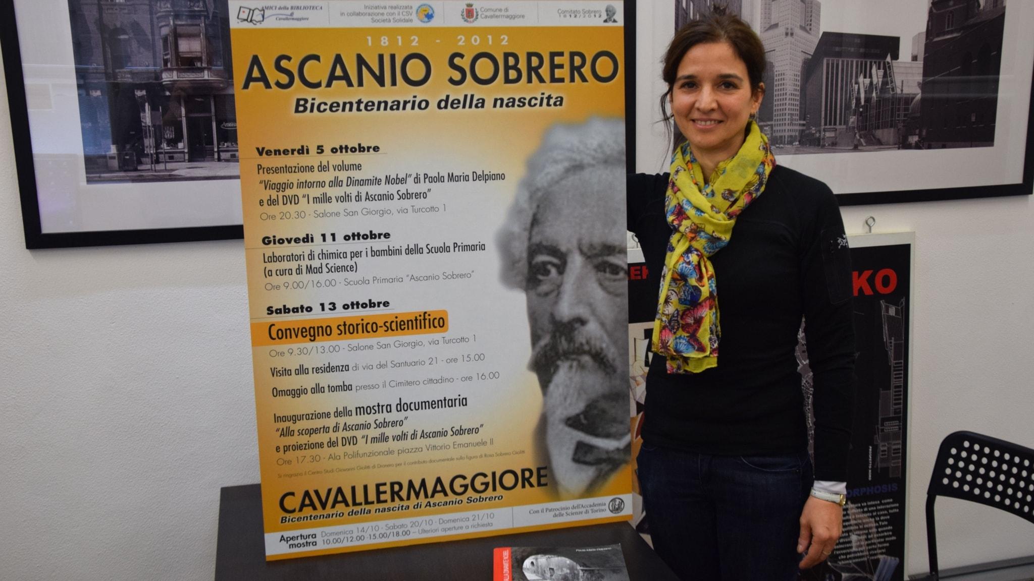 Paola Maria Delpiano framför en affisch