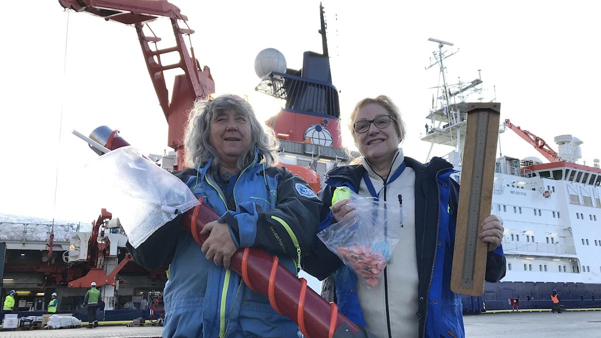 Två kvinnor som håller i avlånga föremål och står på kajen framför ett fartyg.