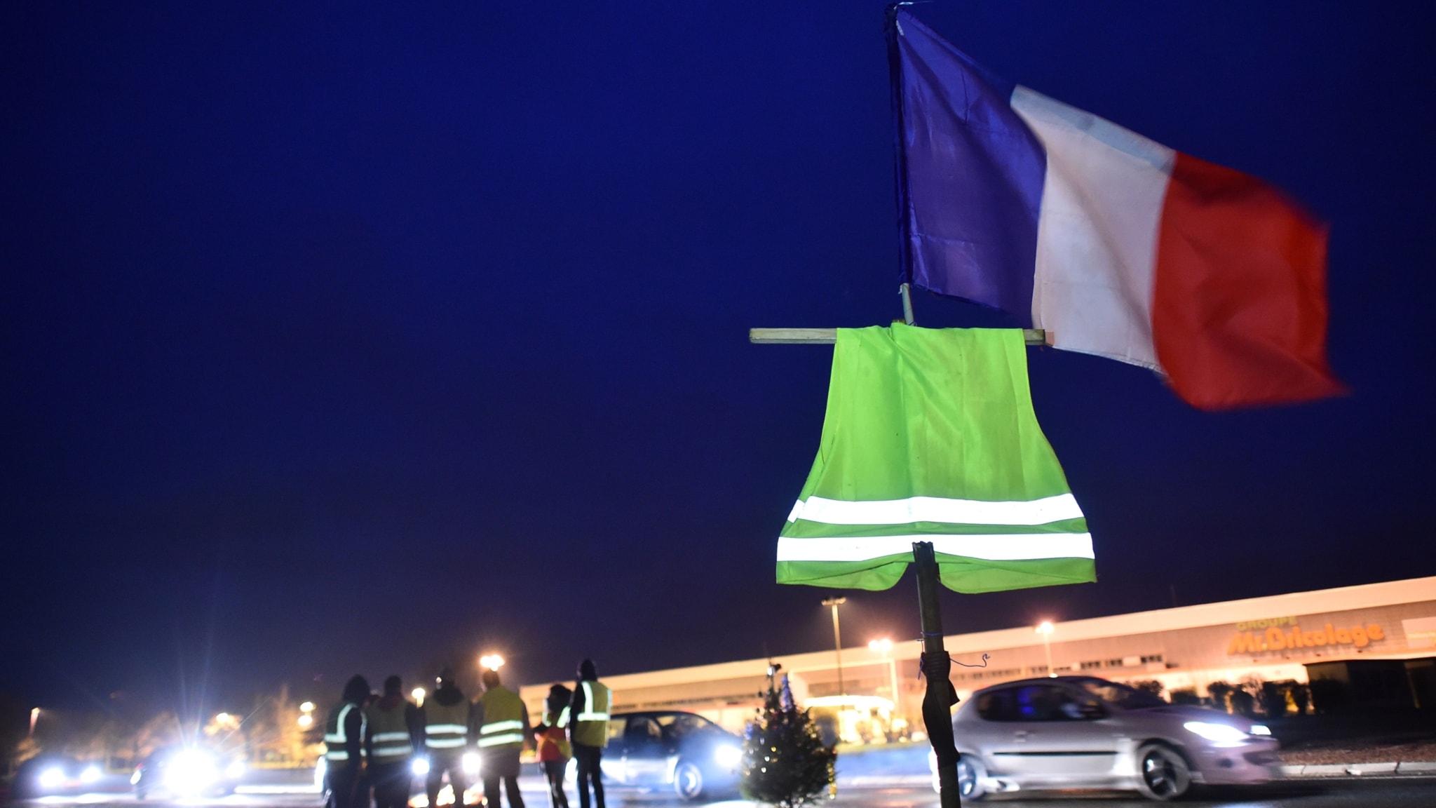 En fransk flagga och en gul trafikväst vajar på en flagstång i skymningen. I bakgrunden en massa bilar och protestanter på en väg.