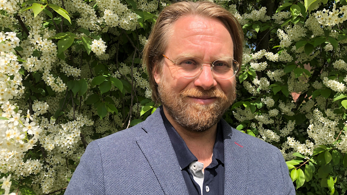 Erik Hemmingsson framför en blommande hägg