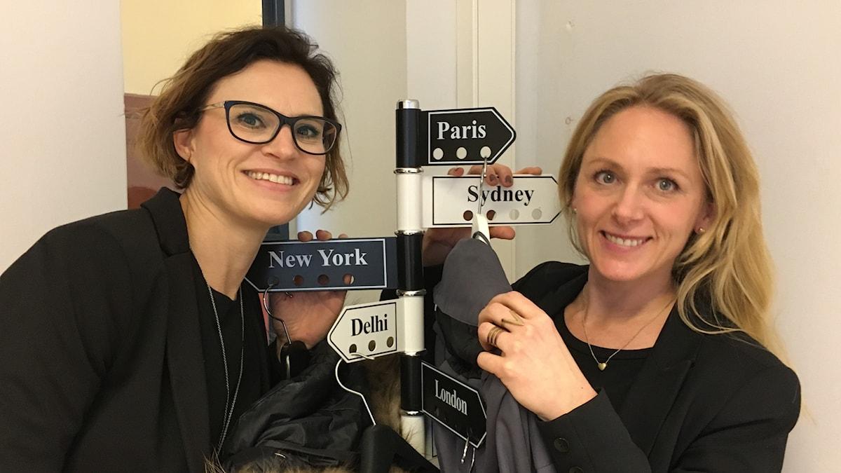 Två kvinnor, en mörkhårig och en ljushårig, ler mot kameran De hänger upp sina jackor på en klädhängare med pilar som har namn på europeiska huvudstäder.
