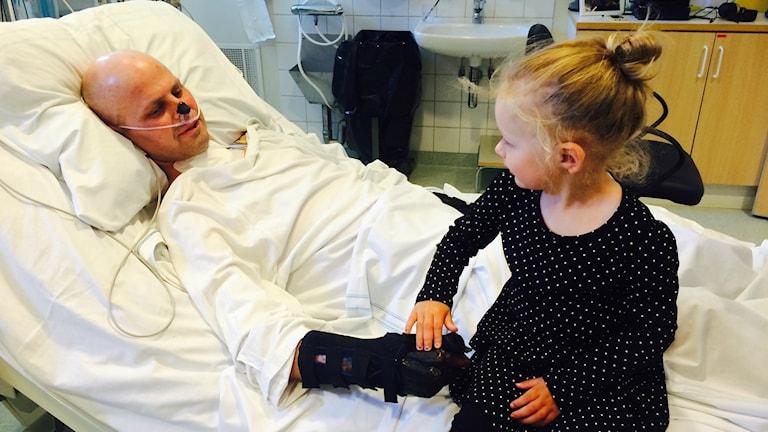 Dottern håller pappas hand i sjukhussängen
