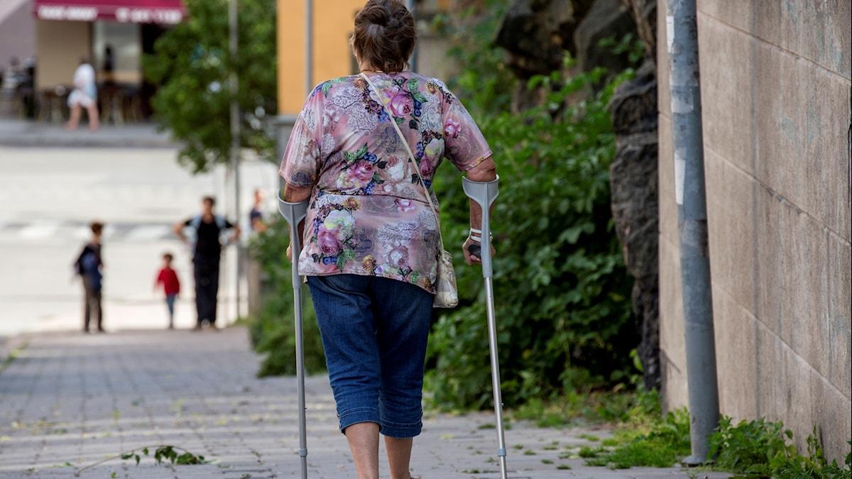 En kvinna går med kryckor på en trottoar